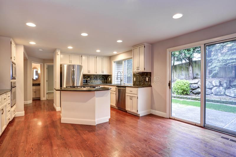 White kitchen room with stainless steel appliances. White kitchen room boasts stainless steel appliances, granite counters, walk-in pantry, island with gas cook stock photography