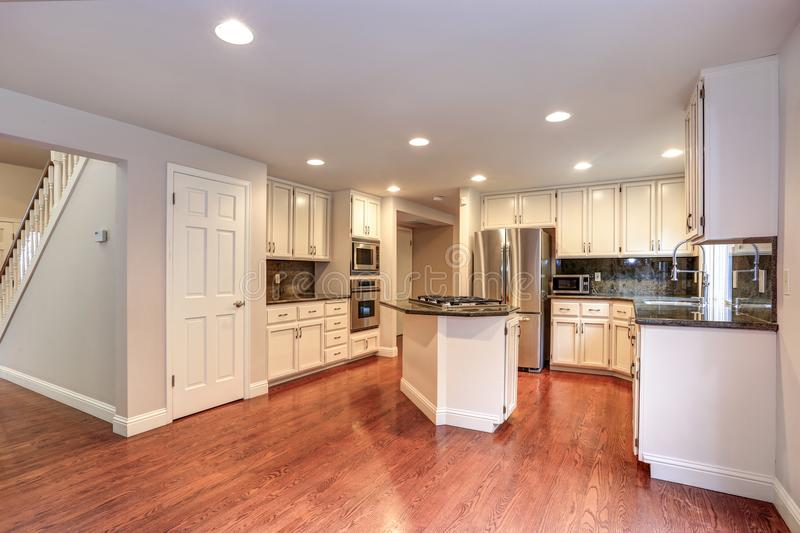 White kitchen room with stainless steel appliances. White kitchen room boasts stainless steel appliances, granite counters, walk-in pantry, island with gas cook stock photos