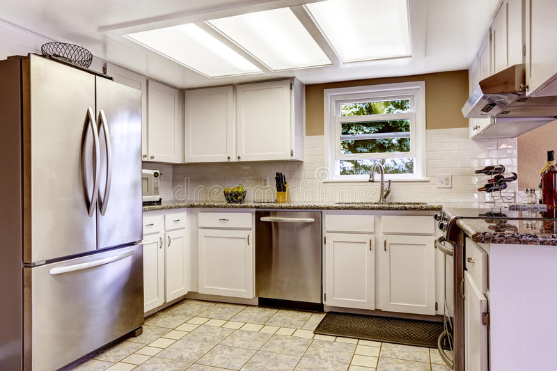 White kitchen room with steel appliances and tile backsplash trim. White kitchen room with slylight and small window. White cabinets blend with steel appliances royalty free stock image