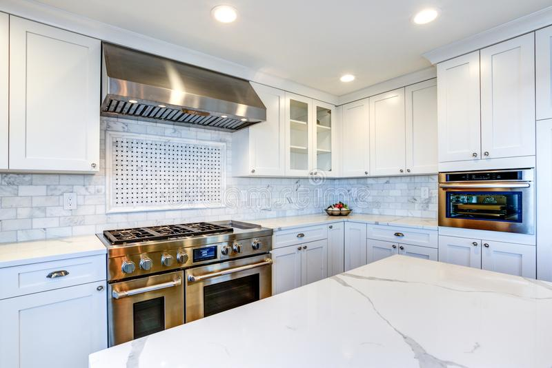 White Kitchen with stainless steel hood over gas cooktop. White Kitchen with stainless steel hood over gas cooktop and carrera marble backsplash stock photography