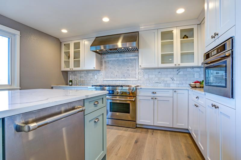 White Kitchen with stainless steel hood over gas cooktop. White Kitchen with stainless steel hood over gas cooktop and carrera marble backsplash stock images