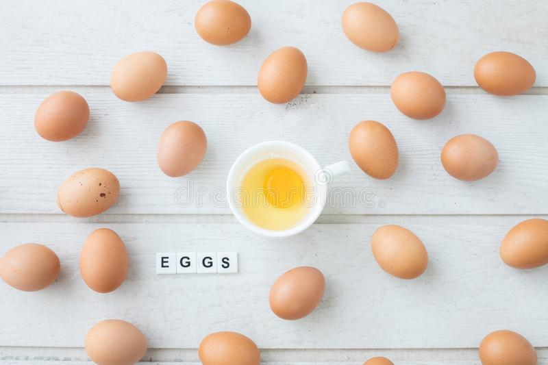 White kitchen table texture background with fresh yellow yolk egg on white cup and eggs text letter. View from top table royalty free stock photography