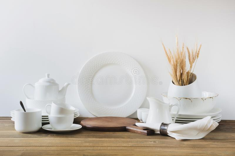 White kitchen utensils, dishware and other different white stuff for serving on white wooden board. royalty free stock photos