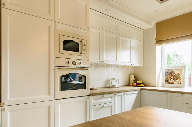 White kitchen wall with microwave and oven. Big window on the right wall stock images