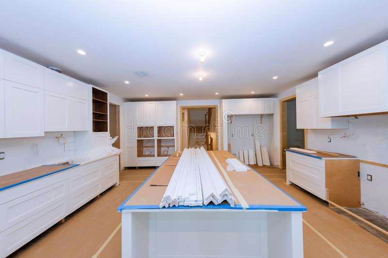 White of kitchen wooden cabinets with contemporary look. Of installation base for island in center, home, assembling, furniture, interior, construction, repair stock image