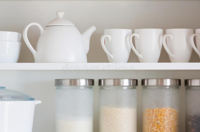 White kitchenware. Opened cupboard with kitchenware inside stock photography