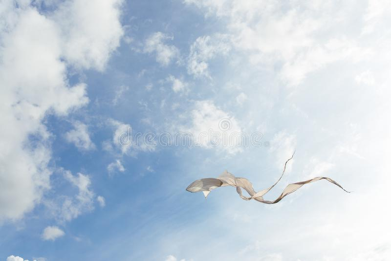 White kite flying against the blue sky full of clouds. Horizontal image.  royalty free stock photo