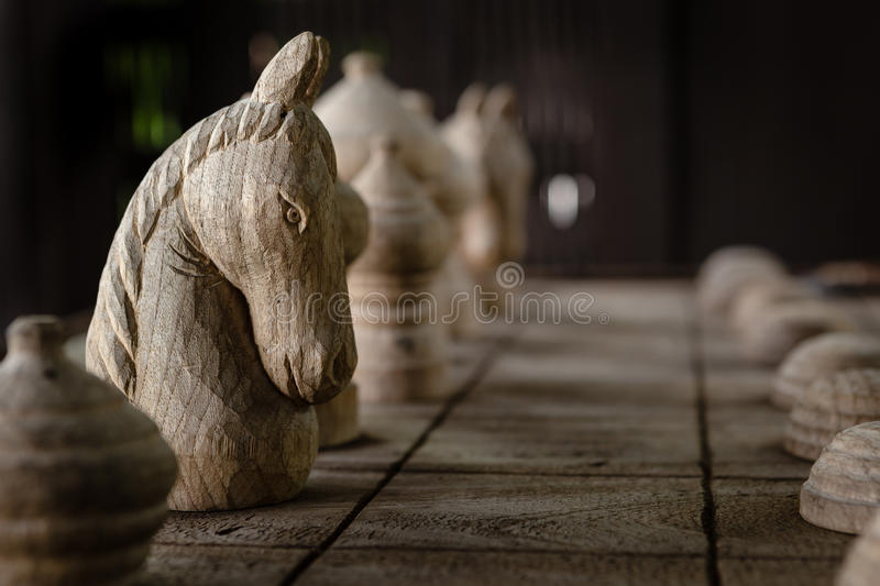 The White knight on the wood chess board. stock photos