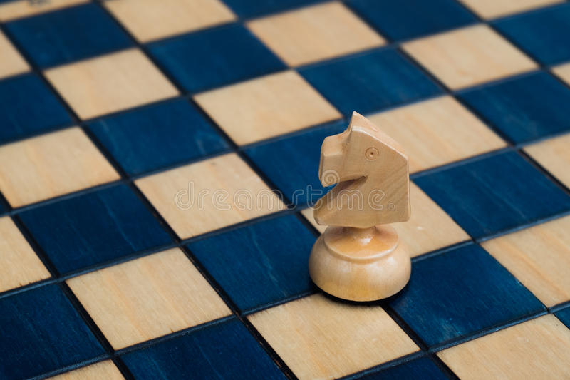 White knight on wooden chessboard. Wooden white blue chess set stock image