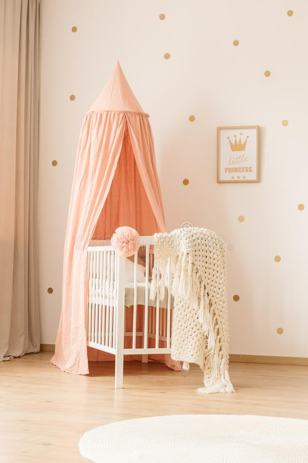 Pink kid`s bedroom interior. White, knit blanket on crib with pink canopy in kid`s bedroom interior with gold poster royalty free stock photo