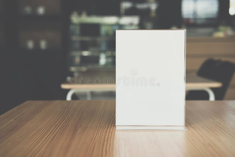 White label in cafe. display stand for acrylic tent card in coffee shop. mockup menu frame on table in bar restaurant. Space for text royalty free stock photo