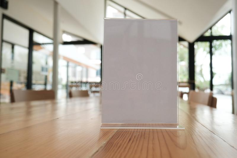 White label in cafe. display stand for acrylic tent card in coffee shop. mockup menu frame on table in restaurant. space for text. White label in cafe. display stock photography