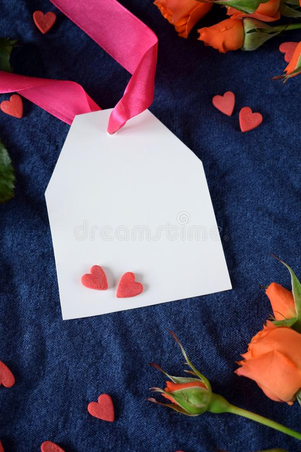 White label with a pink ribbon surrounded by little hearts and orange roses. Copy space for congratulation on Valentine`s day stock images