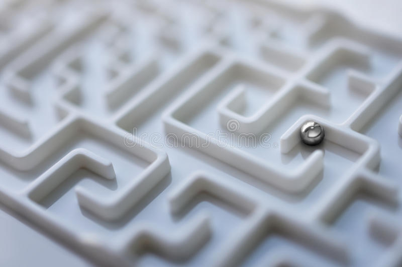 White labyrinth and metal ball, complex problem solving concept. Close up white labyrinth and metal ball, complex problem solving concept royalty free stock photography