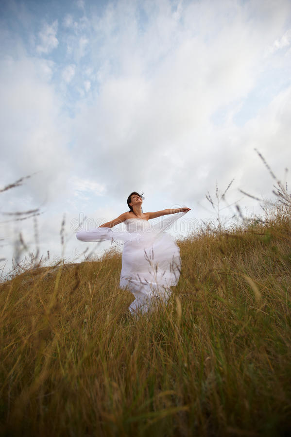 White lace dove (bride in nature). Beautiful bride expressing her happiness with twirls filled with laughter stock images