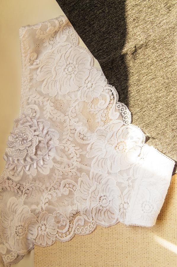 White lace sexy women`s panties against the bright sunlight. Vertical shot, top view, flat lay.  stock image