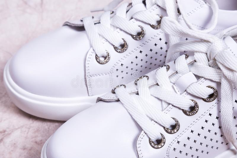 White laced sneakers close-up. Female sneakers in hole on beige background royalty free stock images
