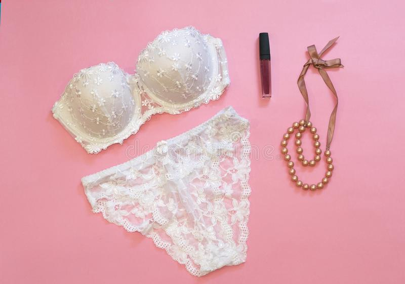 White lacery lingerie near lipstick and necklace on pink background. Woman underwear for special occasions. Composition for beauty royalty free stock image