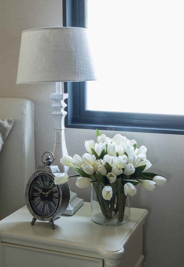 White lamp and alarm clock. On bedside table royalty free stock photo