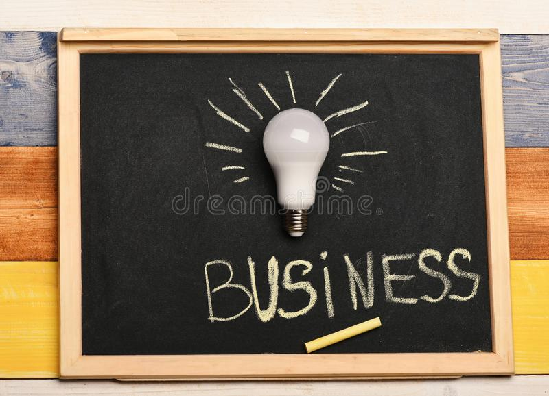 White lamp as symbol of successful business idea. Light bulb and piece of chalk on colorful background. Board with business idea lamp and yellow chalk on grey royalty free stock images