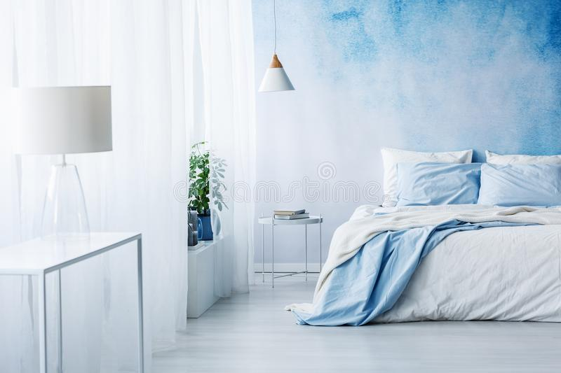 White lamp on a table in bright blue bedroom interior with bed a royalty free stock image