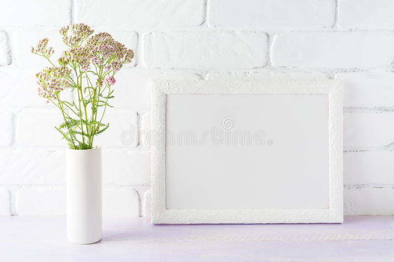 White landscape frame mockup creamy pink flowers in cylinder vase. White landscape frame mockup with creamy pink flowers in cylinder vase near painted brick wall royalty free stock images