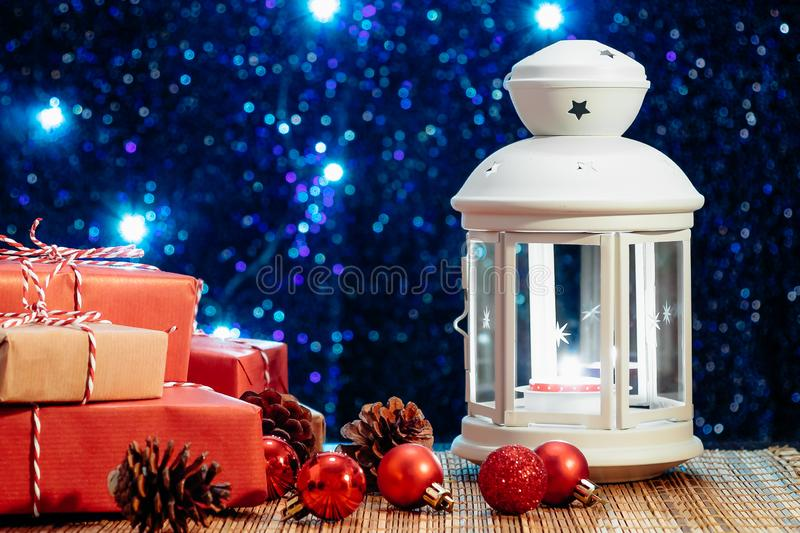 White lantern with a burning candle and boxes with gifts on the background of the Christmas tree with lights. Beautiful royalty free stock photography