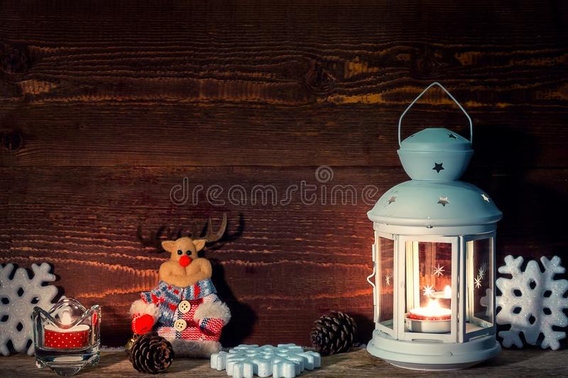 White lantern with a burning candle, cones, a toy deer candle and snowflakes on the background of a wooden wall. Christmas border for greeting card or royalty free stock images