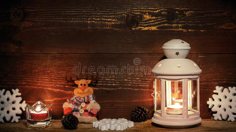 White lantern with a burning candle, cones, a toy deer candle and snowflakes on the background of a wooden wall. Christmas border for greeting card or stock photo