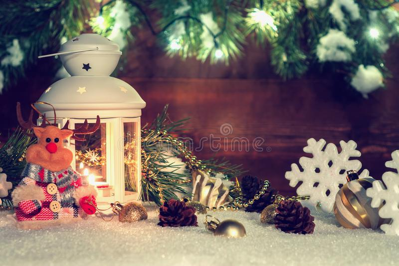 White lantern with a burning candle stands in the snow surrounded by Christmas decorations on the background of a wooden stock photos