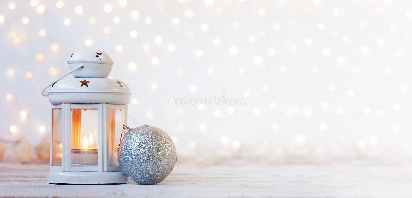 White lantern with candle and silver ball - Christmas decoration. Banner. royalty free stock photography