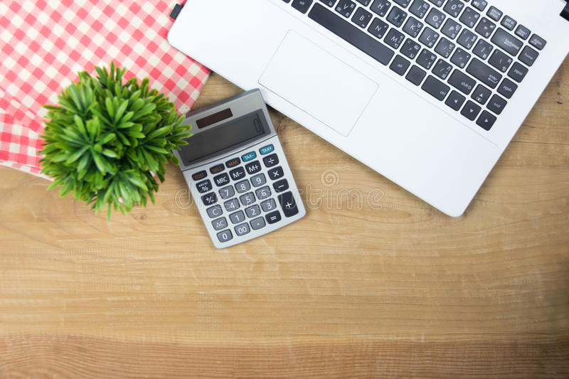 White Laptop and calculator on wooden stock photography