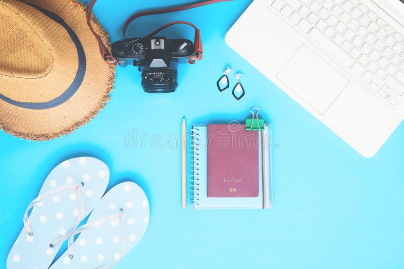 White laptop computer with woman accessories, camera and passport on blue color background, Summer travel stock images