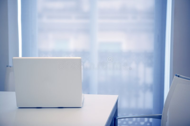 White laptop open on a white room, blue light stock photography