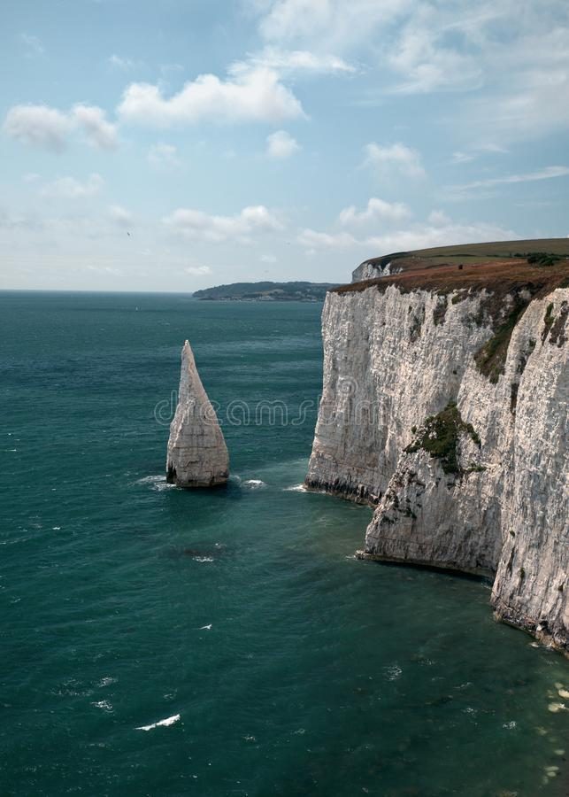 White large sharp rock in the turquoise sea. In Ballard Down. August - 2019. Swanage, England royalty free stock image
