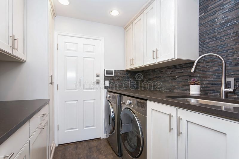 White laundry room boasts white shaker cabinets royalty free stock photos
