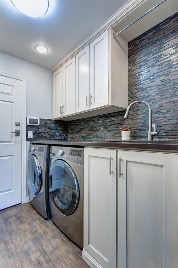 White laundry room boasts white shaker cabinets royalty free stock image