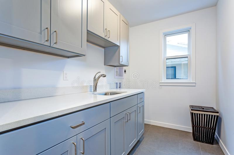 White laundry room with pale gray shaker cabinets stock image