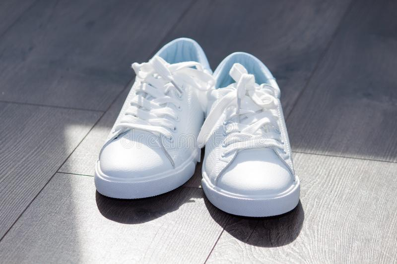 White female sneakers shoes on laces on grey brown wooden background. Shy girl content stock photo