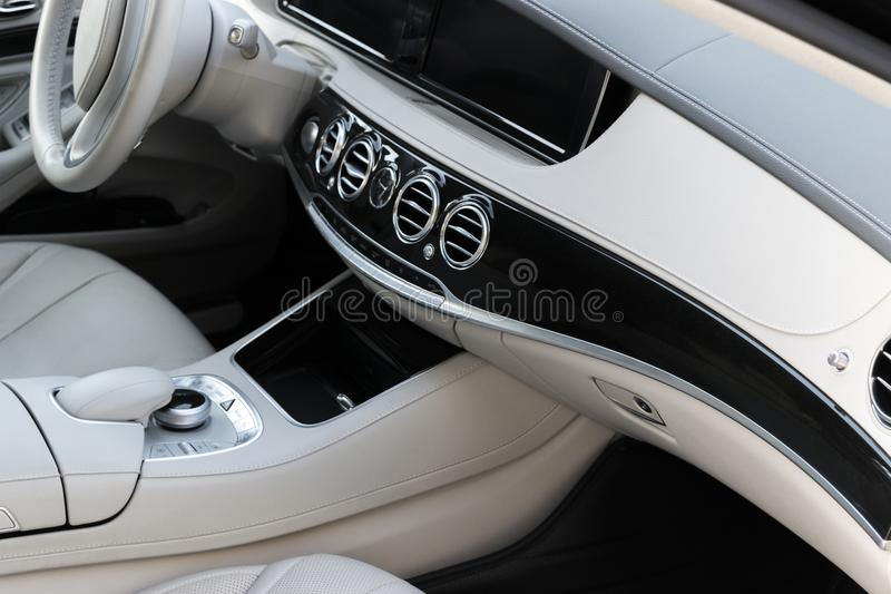 White leather interior of the luxury modern car. Leather comfortable white seats and multimedia. Steering wheel and dashboard. Automatic gear shift. Car royalty free stock photo
