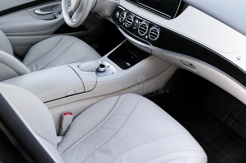 White leather interior of the luxury modern car. Leather comfortable white seats and multimedia. Steering wheel and dashboard. Automatic gear stick stock photography