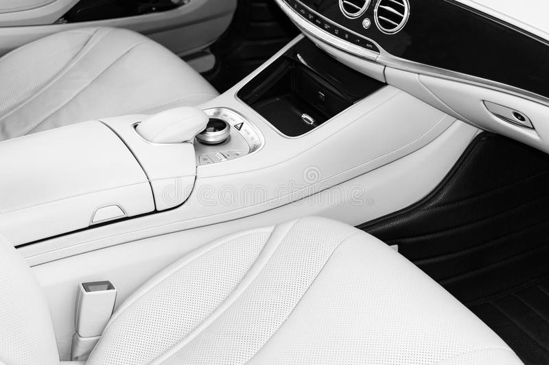 White leather interior of the luxury modern car. Leather comfortable white seats and multimedia. Steering wheel and dashboard. Aut. Omatic gear shift. Car royalty free stock photography