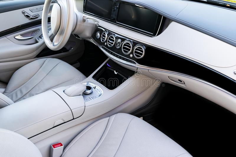 White leather interior of the luxury modern car. Leather comfortable white seats and multimedia. Steering wheel and dashboard. Automatic gear stick. Modern car royalty free stock image