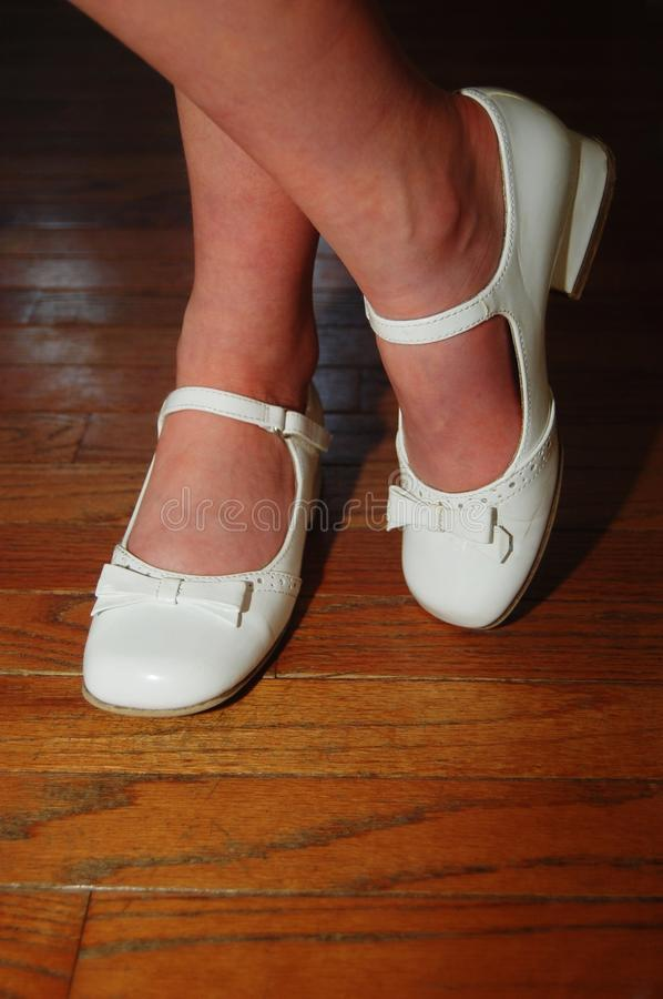 White leather shoes. White patent leather shoes crossed hardwood floor stock images