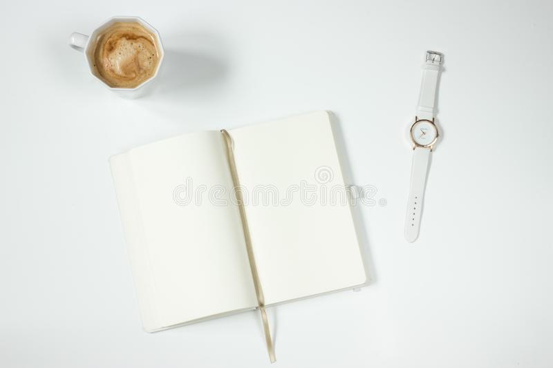 White Leather Strap Silver Round Analog Watch Next to Notebook stock image