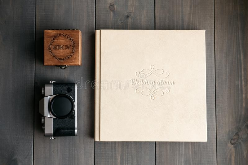 White leather wedding album, wooden box with inscription Wedding day and vintage photo camera. On wooden background stock image