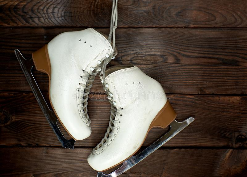 white leather womens skates for figure skating hang on a nail royalty free stock photo