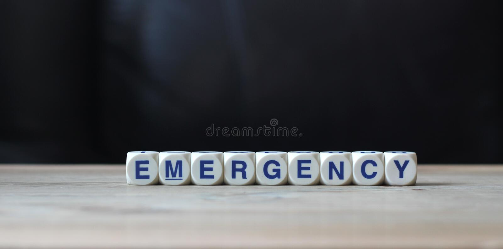Emergency. White letter cubes on table and black background word emergency stock images