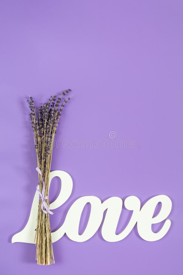 White letters forming word LOVE written with beautiful dried lav. Ender bouquet on violet surface. Top view, copy space. St. Valentine`s Day, wedding holiday royalty free stock photography