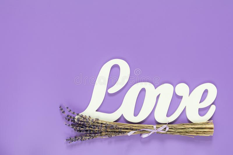 White letters forming word LOVE written with beautiful dried lav. Ender bouquet on violet surface. Top view, copy space. St. Valentine`s Day, wedding holiday royalty free stock images